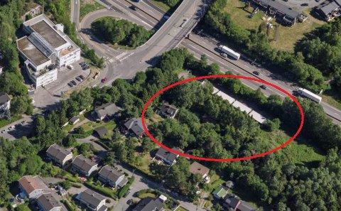 Eiendommen ligger som et grønt belte mellom boligbebyggelsen og E6. I det innringede området ser du en gammel husmannsplass som ønskes bevart og gamle garasjerekker. Sandstuveien er til venstre i bildet.