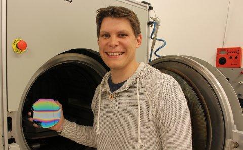 Henrik Sønsteby med en silisiumskive som er dekket med en tynn film bestående av natrium, kalium, niob og oksygen. Dersom det lykkes å produsere den i stor skala, kan du og jeg ha en bit av en slik i mobilene våre om noen år.