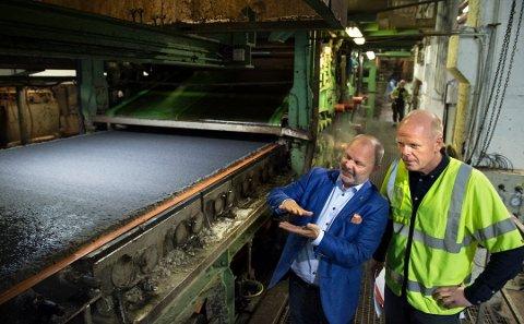 OPTIMISME: HR-sjef Tore Bergsveen i Hunton (tv) viser avdelingsdirektø Jan Tore Stø i NAV Oppland bedriftens asfaltplatepresse. Hunton er en av bedriftene der optimismen råder.