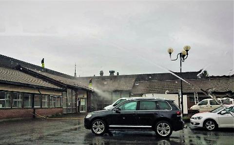 En tipser sendte dette bildet av to som arbeidet med å spyle taket på legesenteret i Sandnessjøen. Ut fra bilde og video (nederst i saken) kommer det fram at de ikke er sikret mot fall. Til tross for at bedriften og Alstahaug kommune sier noe annet.