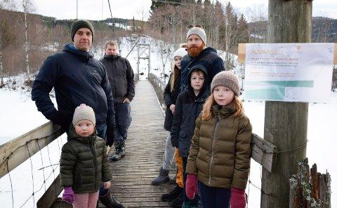 ADVARSEL: Espen Sjøberg foran til venstre med Helene og Tuva,  Lars Hauge til høyre med Isabell og Oskar og Jørgen Støa bakerst til venstre vil gjerne beholde hengebrua, selv om kommunen har hengt opp en advarsel.