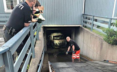 TAUET VEKK: Her blir den utbrente bilen tauet ut av garasjeanlegget etter brannen.