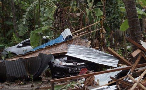 Biler er gravlagt i vrak etter tsunamien som traff flere strender og kystbyer i Indonesia