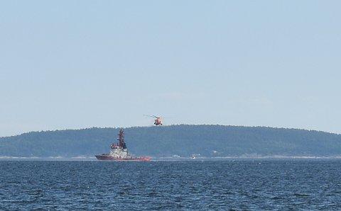 MULIG SØK: Rett sør for Bastøya henger et helikopter lavt over sjøen rett bak en stor slepebåt.
