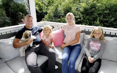 PÅ TERRASSEN: Felicia og Fredrik Zachariassen på terrassen med Ella (5) og Mari-Elle (10). Voffi, sitter på armen til Fredrik, og i huset er det også to katter. Kjelleren har en utleieleilighet hvor en person bor. – Vi trives kjempegodt i Holmestrand, sier de. Foto: Pål Nordby