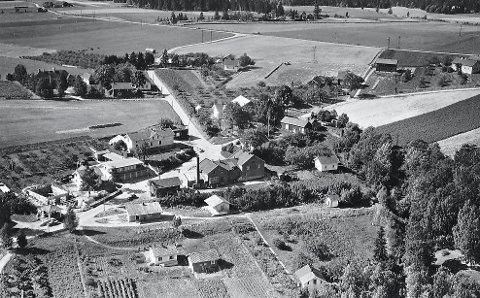 Sylling sentrum 1949: I nedre, midtre del av bildet ligger det tre bygninger på rekke langs den gamle linjetraseen til Lierbanen. Det første huset til venstre (merket med sort pil) er stasjonsbygningen der poståpneriet holdt til i årene 1927-1956. Så følger pakkbua og det vesle huset helt til høyre som er den nedre delen av vanntårnet. Ved bakken, helt nederst til høyre, ligger huset til poståpner Einar Halvorsen. Foto: Widerøes Flyveselskap A/S. Lier Historielags bildesamling