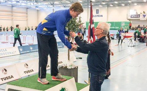 GULL: Sondre Guttormsen mottar sitt første senior-gull i NM. Det kom på 60 meter hekk inne i Ulsteinhallen. Til helgen skal 17-åringen delta på seniorlandskamp i nettopp 60 meter hekk.
