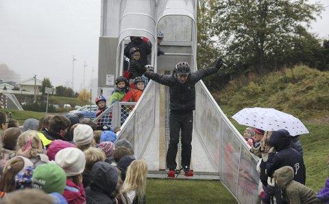 Anders Jacobsen stilte opp til åpningen av den nye hoppbakken på Vang skole i Haugsbygd. Her tar han bakkens første hopp, før han hjelper barna på med skiene.