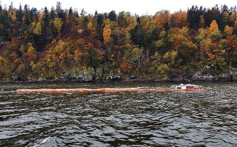 DELVIS UNDER VANN: Båten ligger delvis under vann, og brannvesenet har lagt lenser rundt den.