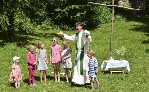 Menighetene har flere ganger tidligere arrangert familiegudstjeneste på Furøya. Her er sogneprest Eckhard Graune og barn fra barnekoret Levende lys under denne gudstjenesten i fjor sommer. Søndag blir det også drop in-dåp her. Privat foto
