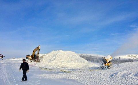 Fra toppen av alpinanlegget på Beitostølen der anleggsarbeidet pågår for fullt, med gravemaskin og preppemaskin, for å rigge de enorme snøhaugene som skal til, før gravemaskin skal skjære ut de gedigne snøkubene.