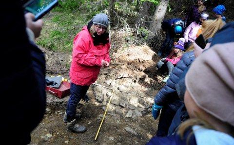 Kulturminne: Arkeolog Nina Hildre viser femteklassingane frå Vestre Slidre skule ei kokegrop dei har funne på eit område litt nord for Gardbergfeltet.