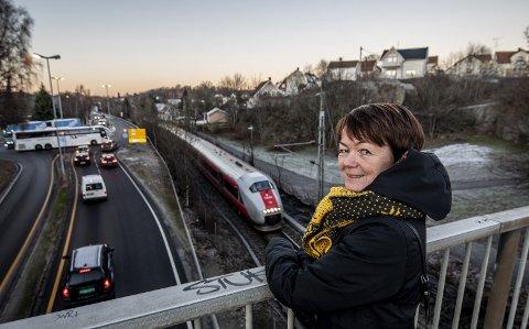 Her blir det forandring: Inn i fjellet rett bak hodet til prosjektleder Elisabeth Nordli vil det sprenges ut tunnel under Kiæråsen, og togsporet vi ser her vil bli fjernet. – Jeg har alltid likt tog, og søkte lokførerutdanningen rett etter videregående uten å komme inn, forteller hun.