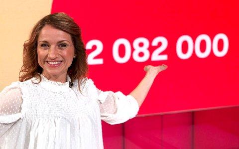 GRATULERTE: Programleder May Lisbeth Midtgård Myrvang viser fram tallpremien som Senja-mannen fikk lørdag.