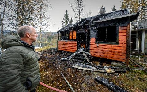 Halvar Tømmermo ser på soveromsvinduet der sønnen Henning hoppet ut og berget seg etter at hytta brant ned natt til torsdag.