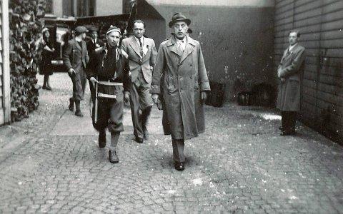 Sigurd Theodor Huse jobbet i NRK i Bergen og var aktiv i Hirden som propagandasjef. Her pågripes han av unge væpnede menn fra hjemmefronten og føres til fengselet sammen med andre NS-folk.