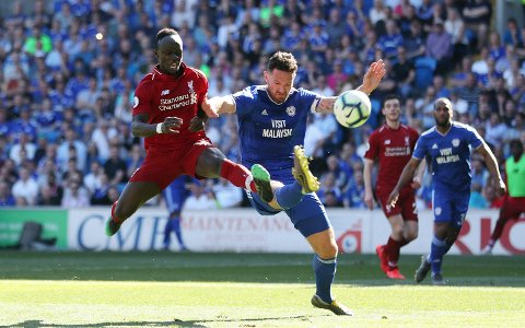 Liverpool's Sadio Mane and Cardiff City's Sean Morrison, right, battle for the ball during the English Premier League soccer match at The Cardiff City Stadium, Cardiff, Wales, Sunday April 21, 2019. (David Davies/PA via AP)