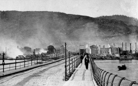 Første bilde av den gamle brua: Året er 1866. En ukjent fotograf tar bilde fra Strømsøsiden av den gamle bybrua like etter den store bybrannen. Vi ser rykende ruiner i bakgrunnen.