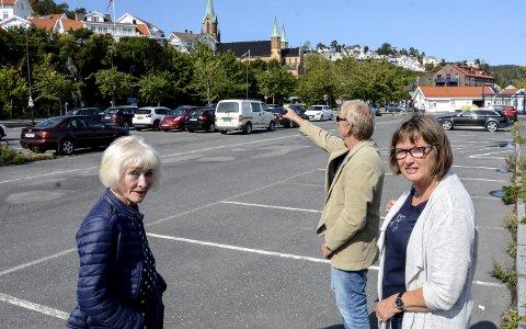 Skeptiske: På denne parkeringsplassen er det planer for et kontorbygg for kommunalt ansatte. Bjørn Olaf Isaksen prøver å se for seg hvor høyt nybygget vil bli. T.v.: Aase Lotsberg og t.h. Anne-Kristin Aas.