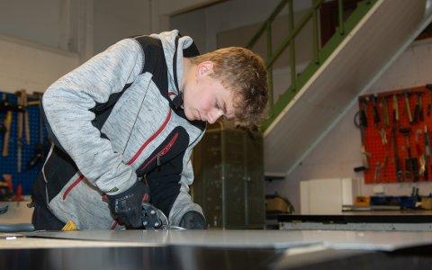 NØYAKTIG: Isak Tøllefsen klipper hjørner i en metallplate, som skal bli topp til pipehatt.