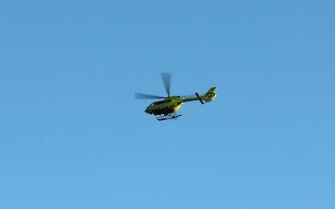 LEGEHELIKOPTER: Et helikopter flyr over området hvor kvinnen i 20-årene ble funnet i Salangselva søndag kveld.