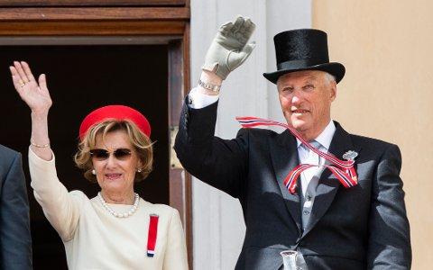 Dronning Sonja og kong Harald i kjent stil, vinkende fra slottsbalkongen 17. mai. Foto: Berit Roald / NTB