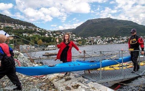 Anna Elisa Tryti setter av penger til en ny bystrand bak seg ved Store Lungegårdsvann. Her har hun selskap av elever og lærere fra Amalie Skram videregående skole som har vært på padletur.