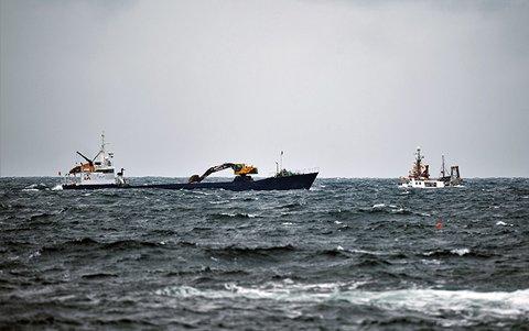 Mindre fiskefartøy i grov sjø utenfor Karmøy, krysser kurs med lasteskip i sandfrakt.