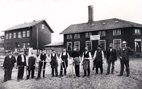 BUGGES GATE. På hjørnet mellom Bugges gate og Kjeld Stubs gate drev Ellef Olsen en trevarefabrikk tidlig på 1900-tallet. Bedriftsbygningen var den gang blant de ytterste i Bugges gate, som bokstavelig talt løp ut i sanden her. I hvilken anledning eieren (t.h.) og de ansatte har tatt oppstilling med sine båndsager, høvler, vinkeljern og tommestokker vites ikke.