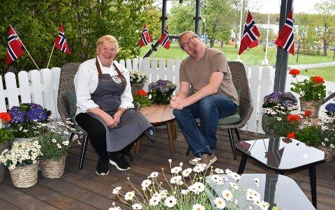 17. MAI-SENDING: Fra Amfiet på Hjertnes blir det festsending fra klokken 12.00 til 15.00. I skrivende stund var kun blomstene på plass, men maten og kaka kommer litt senere. Tv-kokken Nina Lindsholm er alltid «klar som et egg», denne gangen – med sølje på forkleet. Programleder Heljar Berge hadde ikke fått på seg finstasen da bildet ble tatt.  FOTO: Vibeke Bjerkaas