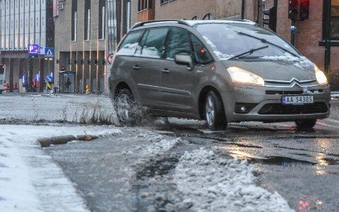 ADVARTE: Det gikk som meteorologene advarte om når de ba bilister kjøre hensynfullt, slaps og dammer ga mye sprut fra bilene. Her ved jernbanebommene i sentrum, der det alltid oppstår en dam når det regner eller sludder.