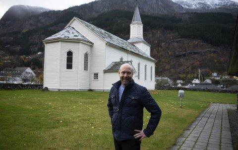 Vikarprest Arne Opsahl-Engen framfor Odda kyrkje. Søndag skal han leia festgudstenesta for kyrkja som er 150 år i 2020. Foto: Eli Lund