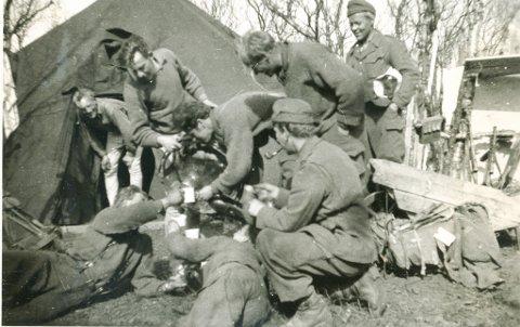 FEIRING FOR FULLE MUGGER: Torgeir Foss (til høyre) følger spent alkoholskjenkingen ved teltet til 2. tropp Riks 1 til polititroppene i Lakselv. Koppene står i kø for å bli fylt opp av etterlatt tysk sprit.