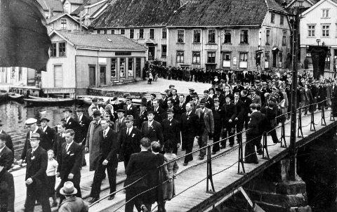 1. mai i Kragerø 1946: Aldri har et 1. mai-tog i Kragerø vært større enn i 1946, ett år etter krigens slutt. Toget er på vei over Jens Lauersøns plass og Bybrua. Bildet viser at mange alvorlige menn deltok. I toget ble det båret en rekke faner, Kragerø Arbeiderparti, ungdomsfylkingen, fagforeningsfaner. Dette var som en marsj inn i en ny tid. Landet skulle bygges – Kragerø skulle bygges. Som bildet også viser, det var ikke så mange som sto langs ruta også på, de aller fleste deltok. Det var samling på Kirketomta, da som, nå.