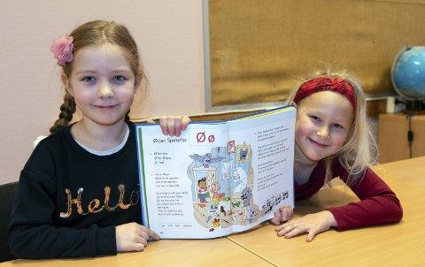 Lesing: Martine Holtermann Røssland (t.v.) og Mariel Hjelmeland Sæbø viser fram leseboka si. Dei to jentene gav Kvinnheringen ein smakebit av historia om spøkelset Ørjan.