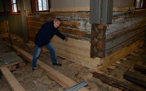 I ORDEN: Sviller og stokker er nå skiftet. Leder i restaureringskomiteen, Eivind Bergem, viser her at man har skiftet ekstra med stokker i hjørnet som var hardest angrepet av råte.