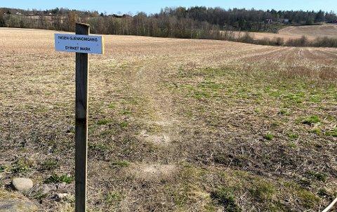 BINDELEDD: Stien som nå er stengt strekker seg omtrent 170 meter over et jorde i Slagendalen. Her er blåmerket fjernet og denne teksten er satt opp.