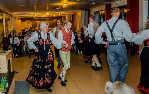 Bunadskledde Tove og Svein Arne Sølvberg viser frem folkedans på Moer sykehjem sammen med resten av Springar'n.