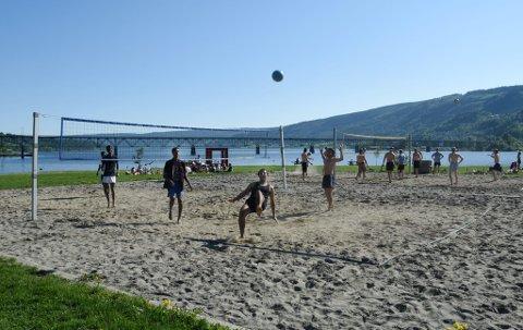 SOLHUNGRIGE: Det sydet av liv på Strandpromenaden på Lillehammer tirsdag ettermiddag. Ali Al-hamdawi (nærmest) og kameratene skal spille volleyball til sola går ned.