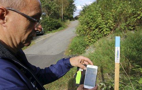 SJEKKER INN: Eivind Tokheim i Odda orienteringslag skanner koden på stolpen og kunne dermed hake av nok en post i mobilapplikasjonen Stolpejakten.