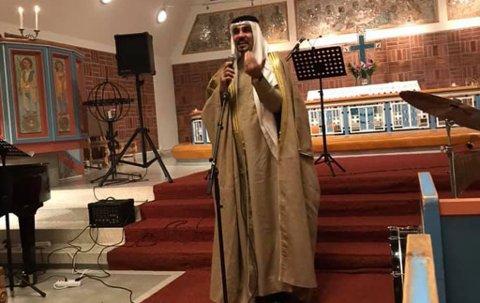 BLE DELT: Dette bildet av Abdullah Bin Zidan (45) kledd i sin irakiske nasjonaldrakt i Hammerfest kirke ble delt flere steder på Facebook. Her leser han to dikt om kjærlighet og flukt.