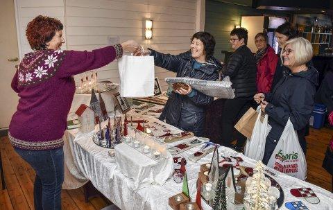 Julegåver: Grete Karin Rørvik (t.v.) frå Sunde hadde ein populær krok. Her rekkjer ho ein pose med varer til ein annan sundebu, Solfrid Olsen, som handlar nokre julegåver med smil om munnen.