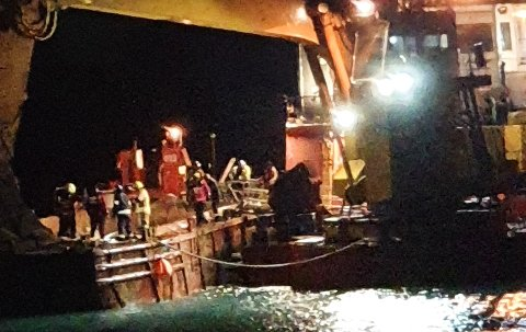 DØDSULYKKE: Her jobbet redningsmannskaper med å hente ut den omkomne Tobias Alfredsen fra Troms. Politiet har foreløpig ikke kommet nærmere noen svar på hva som skjedde på lekteren som var på oppdrag ved havna i Gamvik.