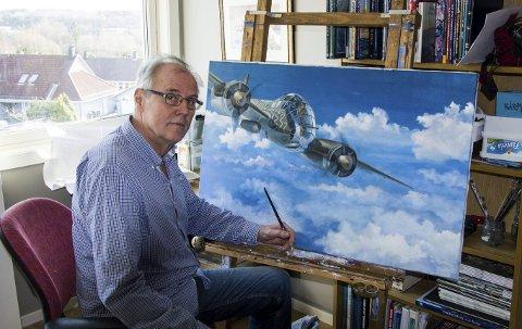 Malerier: Birger Grønberg fordeler tiden sin som pensjonist mellom modellbygging og maling. Bildet han holder på med her viser et tysk kampfly som forbereder seg til å angripe en alliert konvoi på vei til Murmansk.foto: roger W. Sørdahl