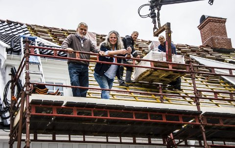 Gleder seg: Per Thorstensen og Hilde Borgir fra Stiftelsen Tollerodden gleder seg til at hele taket blir dekket av svart, glasert takstein. Foreløpig er man godt i gang med sørsiden av taket.foto: roger w. sørdahl