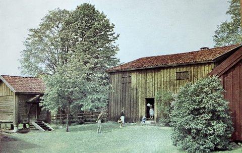 Fargepostkort fra Østfoldtunet som viser Bærbystua, husmannsstua og stabbur. Fotografiet er tatt på slutten av 1950-tallet, og damen i døra er antagelig kårkone Karen Holtet (fra familien settes på museum). (Fotograf: Lauritz Opstad)