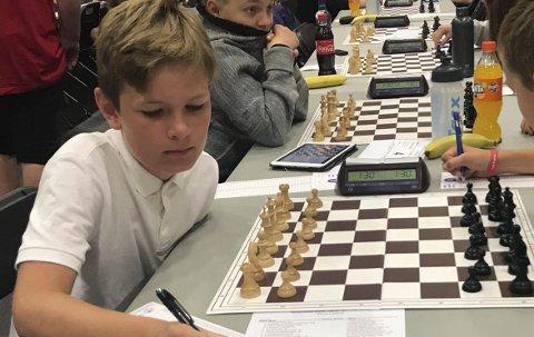SKRIVER NED TREKKENE: Eirik Strøm Austad (12) ved sjakkbrettet under NM i Larvik. Stortalentet endte til slutt på andreplass, etter glimrende spill. Nå venter voksen motstand i neste turnering, når Kragerø Grand Prix går av stabelen i begynnelsen av september.