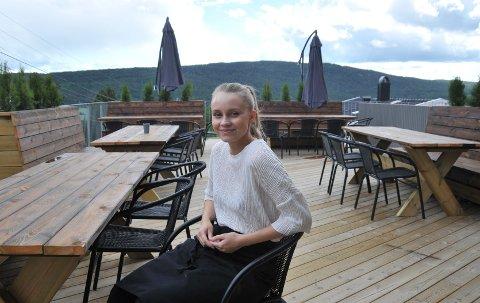 STØRREUTEPLASS:Erika Hexeberg på terrassen til Nybrent som nylig åpnet for gjester, men som ennå ikke er helt ferdig.Ibakgrunnen ser vi Holterkollen.
