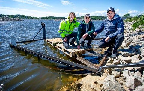 Spente studenter: Etter et par timers rigging og festing av reimer ble konstruksjoen heist ut i Glomma. Studentene Johann Vårvik (24 f.v.), Anders Jamissen (23)  og Henrik Pettersen (24) poserer fornøyd.
