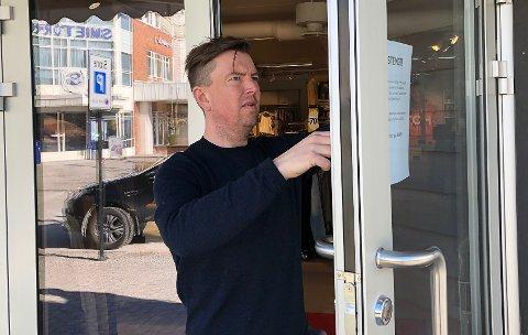 KORONA-STENGT: MIkal Linstad setter opp infolapp og stengte døra i butikken på formiddagen tirsdag.